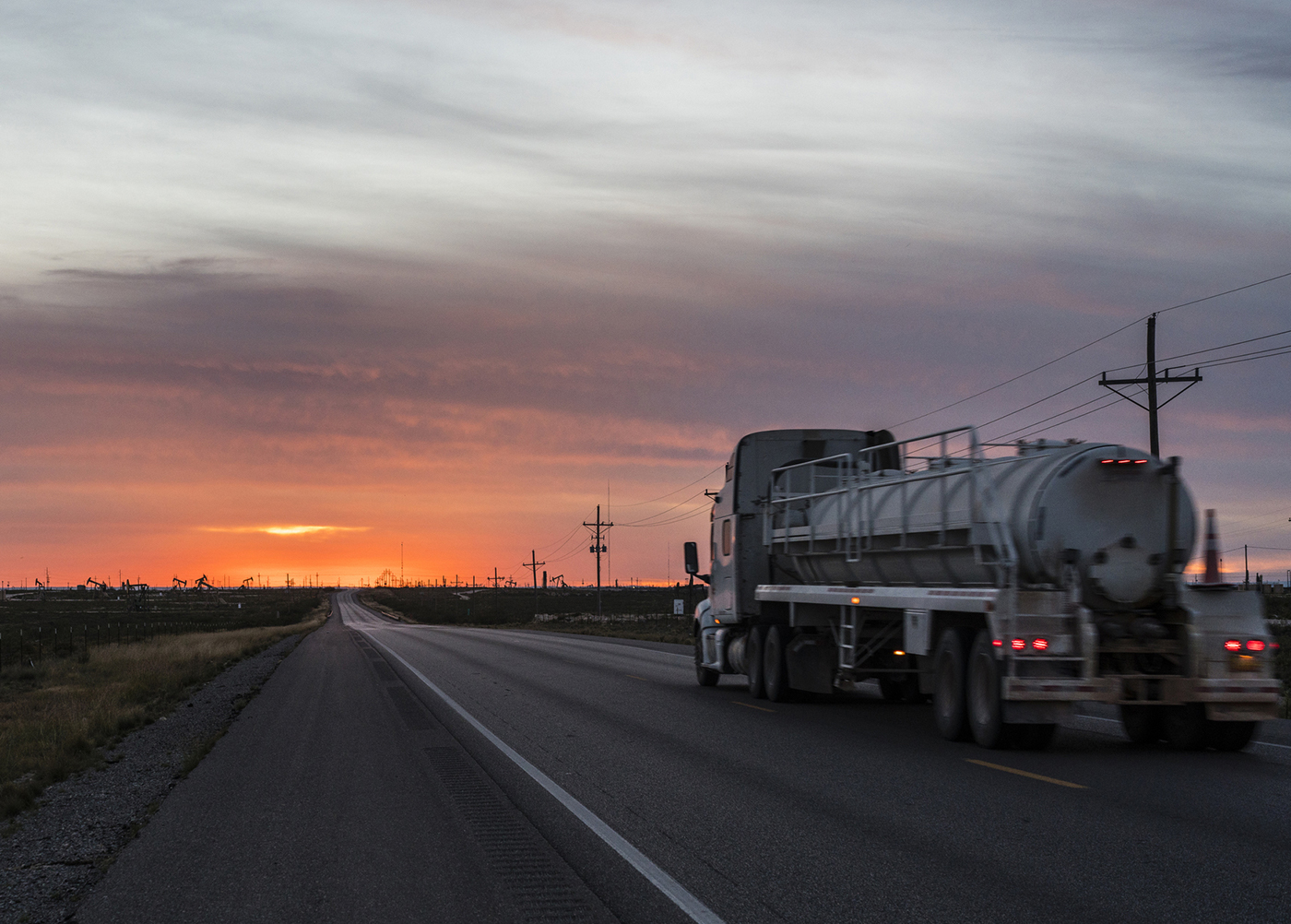 An oilfield truck driving in the sunset on a road in the Permian Basin